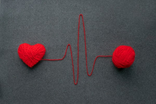 handmade-red-yarn-ball-with-heart-made-of-red-wool-yarn-and-thread-like-ecg-pattern-on-a-gray-woolen_t20_noa8X6